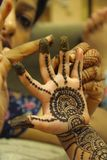 Close-up of woman drawing mehendi or tattoo on little girl`s palm. Pune stock image