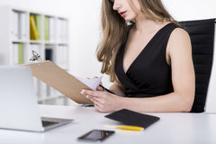 Close up of woman in dress with clipboard Royalty Free Stock Photos
