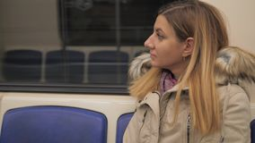Close-Up Woman Dressed In Warm Jacket In Underground Subway Sitting At Window. Young brunette caucasian woman sitting in the underground subway train, dressed in stock footage
