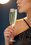 Close up of woman drinking champagne at party Stock Photo