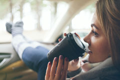 Close-up of a woman drinking take away cup of hot coffee. During the road trip in a car. Selective focus, film effect Stock Photo