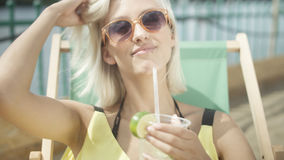 Close up of a woman drinking a tropical mojito cocktail decorated with fresh fruit through a straw on her summer vacation. Stock Photography