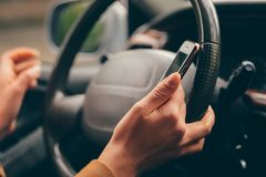Close up woman driving car and using navigation or gps on mobile smartphone. Blurred car interior background royalty free stock images