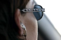 Close up on a Woman Driving with a Headset on Royalty Free Stock Image