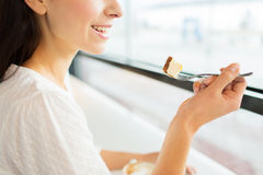 Close up of woman eating cake at cafe or home Stock Images