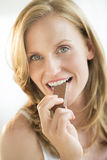 Close-Up Of Woman Eating Chocolate Royalty Free Stock Photography