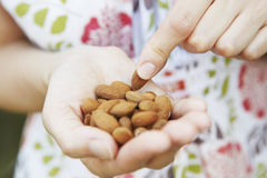 Close Up Of Woman Eating handful Of Almonds stock image