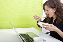 Close up of woman eating at her desk Royalty Free Stock Images