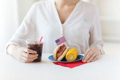Close up of woman eating hot dog with coca cola Royalty Free Stock Images