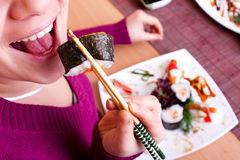 Close up  of woman eating sushi Royalty Free Stock Photo