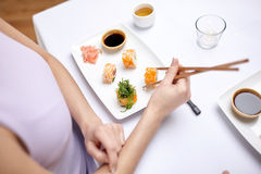 Close up of woman eating sushi at restaurant Stock Photos