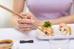 Close up of woman eating sushi at restaurant. Restaurant, food, people, asian and japanese kitchen concept - close up of women eating sush with chopsticks at Stock Images