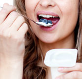 Close-up of a woman eating a yogurt. Isolated on a white background Royalty Free Stock Image