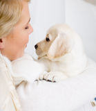 Close up of woman embracing labrador puppy Stock Images