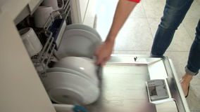 Close Up Of Woman Emptying Crockery From Dishwasher stock video footage