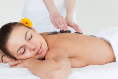 Close up of a woman enjoying a hot stone massage Royalty Free Stock Photos
