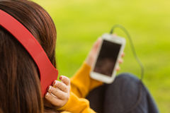 Close up of woman enjoying music in park Royalty Free Stock Images