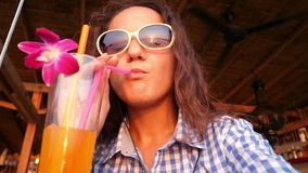 Young pretty woman in sunglasses enjoying tropical cocktail decorated with fresh flower and listen to music in. Close up of woman enjoying tropical mojito stock video