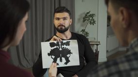 Close-up of woman explaining her vision of Rorschach inkblots. Professional Caucasian male psychologist with black hair