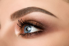 Close-up of woman eye with beautiful brown smokey eyes makeup. Close up of blue woman eye with beautiful brown with red and orange shades smokey eyes makeup royalty free stock photos