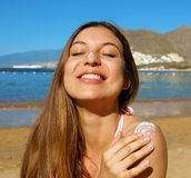 Close up of woman with eyes closed applying sunscream on face and shoulder.  stock photography