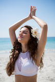 Close up of woman with eyes closed exercising at beach. On sunny day Royalty Free Stock Image