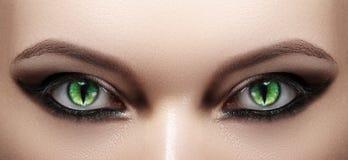 Close-up of Woman Eyes. Halloween Makeup. Cat Eye Lens. Fashion Catwalk Black Make-Up. Luminous Green Cats Eyes. Closeup Shot royalty free stock photography