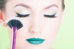 Close-up of woman face wearing professional make-up. Holding brush with eyes closed isolated on green background Stock Images