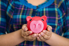Close up woman facing camera, holding piggy bank and placing money inside it, smiling happily Stock Photo
