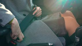 Woman fastening car safety seat belt while sitting inside of vehicle before driving stock footage