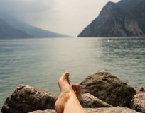 Close up of woman feet relaxing by a beautiful big lake lying on the edge of rocks. Close up feet of woman relaxing by a beautiful big lake lying on the edge of royalty free stock photos