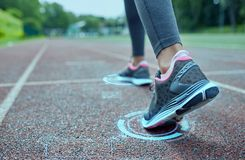Close up of woman feet running on track from back. Fitness, sport, training, people and lifestyle concept - close up of woman feet running on track from back Stock Image