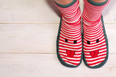 Close up of woman feet wearing funny socks with with happy smiley face. New Year and Christmas time, always be and stay positive c Royalty Free Stock Images
