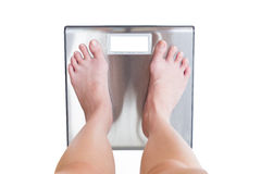 Close-up of woman feet weighing scale isolated on white backgrou Royalty Free Stock Images