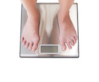 Close-up of woman feet weighing scale isolated on white backgrou Stock Photography