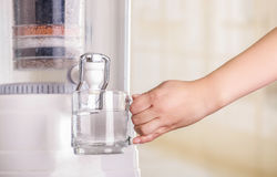 Close up of a woman filling a glass of water, with a filter system of water purifier on a kitchen background Royalty Free Stock Image