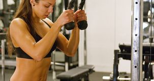Close-up of focused woman training triceps muscles pulling cable machine in gym. Close-up of a woman with fit strong body doing weight exercise for arms in stock video