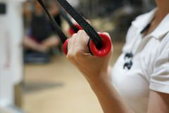 Close up  on  woman flexing muscles on cable gym. In healthy lifestyle concept Royalty Free Stock Photo