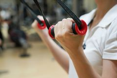 Close up  on  woman flexing muscles on cable gym. In healthy lifestyle concept Royalty Free Stock Images