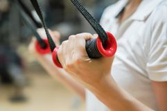 Close up  on  woman flexing muscles on cable gym. In healthy lifestyle concept Royalty Free Stock Photography