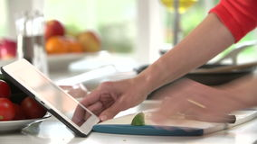 Close Up Of Woman Following Recipe On Digital Tablet