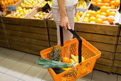 Close up of woman with food basket in market Stock Photo