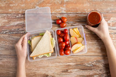 Close up of woman with food in plastic container. Healthy eating, storage, dieting and people concept - close up of woman hands with food in plastic container at Stock Photos