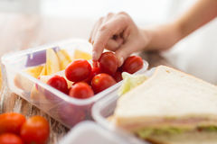 Close up of woman with food in plastic container. Healthy eating, storage, dieting and people concept - close up of woman with food in plastic container at home Royalty Free Stock Photos