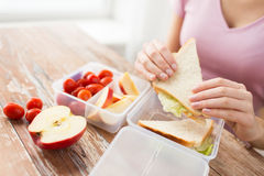 Close up of woman with food in plastic container. Healthy eating, storage, dieting and people concept - close up of woman with food in plastic container at home Stock Images