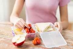 Close up of woman with food in plastic container. Healthy eating, storage, dieting and people concept - close up of woman with food in plastic container at home Stock Photo