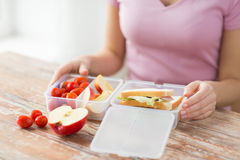 Close up of woman with food in plastic container. Healthy eating, storage, dieting and people concept - close up of woman with food in plastic container at home Stock Photos