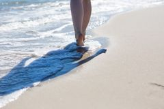 Close up of woman foot walking by sea shore Royalty Free Stock Photography