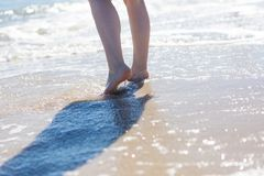 Close up of woman foot walking by sea shore Stock Photo
