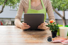 Close up of woman or gardener holding tablet pc. People, gardening, flowers and profession concept - close up of woman or gardener holding tablet pc computer and Royalty Free Stock Photo